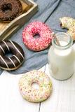 瓶牛奶和五颜六色的油炸圈饼用巧克力和结冰, 库存照片