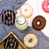 瓶牛奶和五颜六色的油炸圈饼用巧克力和结冰 图库摄影