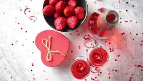 瓶玫瑰色香槟、玻璃用新鲜的草莓和心形的礼物 影视素材