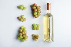 瓶用白葡萄酒和新鲜的成熟水多的葡萄在轻的背景 库存图片