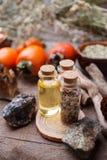 瓶用草本、干燥花、石头和不可思议的对象在巫婆木桌上 免版税库存照片