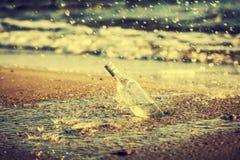 瓶用水在海滩,减速火箭的instagram葡萄酒作用滴下 免版税库存照片