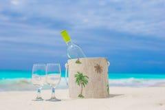 瓶白葡萄酒和两块玻璃在异乎寻常的沙滩 库存图片