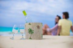 瓶白葡萄酒和两块玻璃在异乎寻常的沙滩 图库摄影