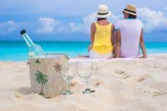 瓶白葡萄酒和两块玻璃在沙滩的背景愉快的夫妇 免版税库存图片