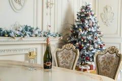 瓶白葡萄酒和玻璃在桌上在美好的holdiay装饰的室圣诞节庆祝的 新年度 免版税库存图片