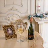 瓶白葡萄酒和玻璃在桌上在美好的holdiay装饰的室圣诞节庆祝的 新年度 免版税库存照片
