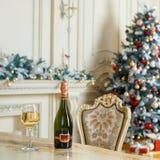 瓶白葡萄酒和玻璃在桌上在美好的holdiay装饰的室圣诞节庆祝的 新年度 库存图片