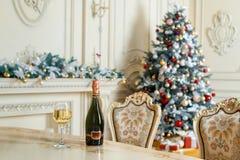 瓶白葡萄酒和玻璃在桌上在美好的holdiay装饰的室圣诞节庆祝的 新年度 库存照片