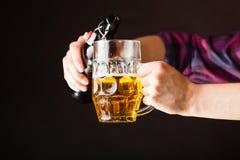 年轻从瓶的人倾吐的啤酒到杯子里 免版税库存照片