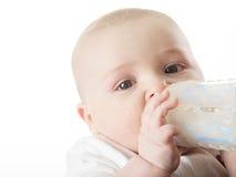 从瓶的俏丽的男婴饮用奶 免版税图库摄影