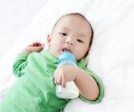 从瓶的俏丽的男婴饮用奶 免版税库存图片