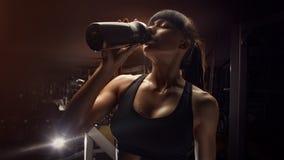 从瓶的健身妇女饮用水 免版税图库摄影