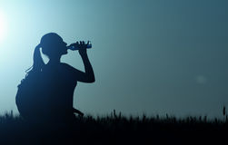 从瓶的妇女饮用水在日落 库存图片