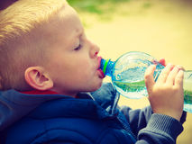 从瓶的小的渴男孩儿童饮料水 库存照片