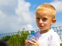 从瓶的小的渴男孩儿童饮料水 图库摄影