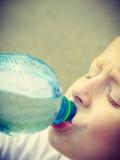 从瓶的小的渴男孩儿童饮料水 免版税库存图片