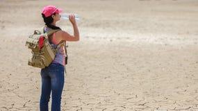 从瓶的旅行家饮用水在沙漠 免版税库存照片