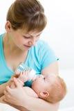 从瓶的母亲哺养的婴孩 库存图片