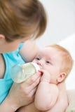 从瓶的母亲哺养的婴孩 免版税库存图片