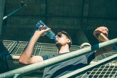 从瓶的热的夏日年轻人饮用水 免版税库存照片