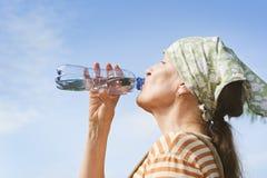 从瓶的资深妇女饮料水 免版税库存图片