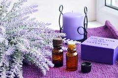 瓶精油、肥皂和蜡烛用淡紫色 免版税库存照片