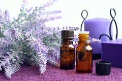 瓶精油、肥皂和蜡烛用淡紫色 免版税库存图片