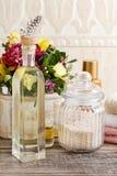 瓶精油和瓶子在木桌上的海盐 免版税库存照片