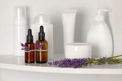 瓶精油用在架子的淡紫色 免版税图库摄影