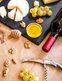 瓶红葡萄酒、开胃菜和拔塞螺旋在木backgroun 图库摄影