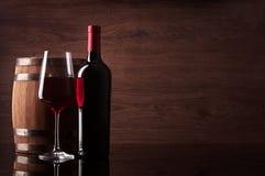 瓶红葡萄酒、玻璃和桶在木背景 库存图片