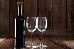 瓶红葡萄酒和两块空的玻璃 免版税图库摄影