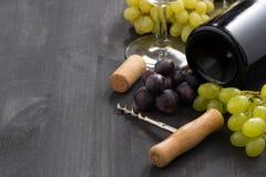 瓶红葡萄酒和葡萄在木背景 免版税库存照片