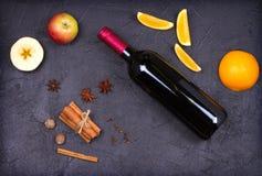 瓶红葡萄酒和被仔细考虑的酒成份在黑背景 香料和果子热的酒精饮料的 免版税库存图片
