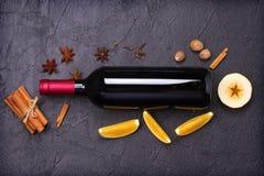 瓶红葡萄酒和被仔细考虑的酒成份在黑背景 香料和果子热的酒精饮料的 库存照片