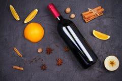 瓶红葡萄酒和被仔细考虑的酒成份在黑背景 香料和果子热的酒精饮料的 免版税图库摄影