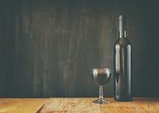 瓶红葡萄酒和酒杯在木桌 图象被过滤, instagram样式 库存照片