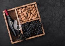 瓶红酒和空的玻璃用黑暗的葡萄与黄柏和拔塞螺旋在葡萄酒木箱里面在黑石背景 免版税库存照片