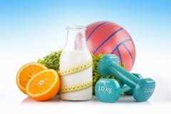瓶蛋白质饮料包裹与一卷黄色测量的磁带用绿色莴苣、桔子、橡胶手球和蓝色健身dumbbel 免版税库存图片
