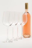 瓶被排行的玫瑰色酒葡萄酒杯 免版税图库摄影
