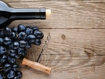 瓶酒、拔塞螺旋和葡萄 免版税库存照片