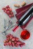 瓶酒、酒杯、葡萄和拔塞螺旋在灰色背景 免版税库存图片
