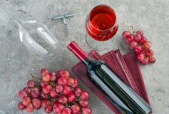 瓶酒、酒杯和葡萄在灰色背景 免版税库存照片