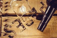 瓶酒和一个空的葡萄酒杯在一个年迈的木箱子,顶视图,选择聚焦 免版税图库摄影