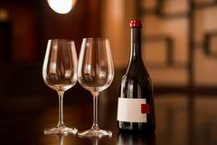 瓶酒和两块玻璃在桌上 免版税库存图片