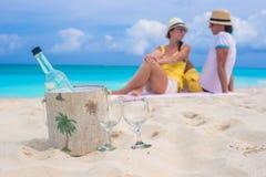 瓶酒和两块玻璃在海滩的背景愉快的夫妇 免版税库存照片