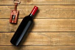 瓶酒和拔塞螺旋在木背景 与拷贝空间的顶视图 图库摄影