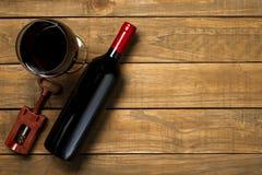 瓶酒和拔塞螺旋在木背景 与拷贝空间的顶视图 免版税库存图片