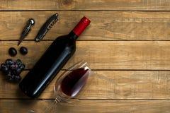 瓶酒和拔塞螺旋杯子和葡萄在木背景 与拷贝空间的顶视图 图库摄影